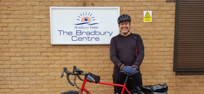 Cyclist stood next to red bicycle outside. He is standing next to the Bradbury Centre sign.