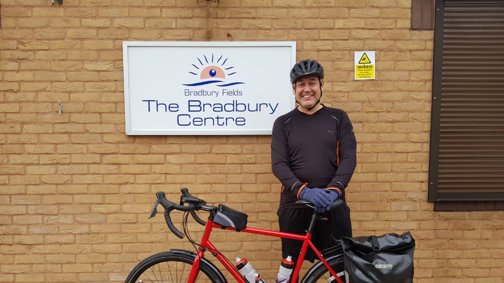 http://Cyclist%20stood%20next%20to%20red%20bicycle%20outside.%20He%20is%20standing%20next%20to%20the%20Bradbury%20Centre%20sign.