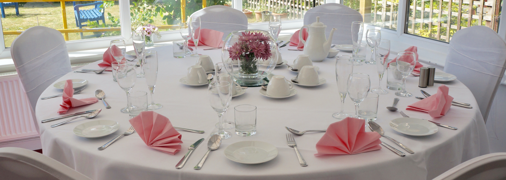http://A%20close-up%20of%20an%20eight%20place%20setting%20for%20afternoon%20tea%20with%20white%20linen%20and%20pink%20napkins.%20The%20chairs%20are%20dressed%20with%20white%20covers%20and%20large%20organza%20bows.%20The%20pastel%20coloured%20bunting%20frames%20the%20window%20showing%20the%20sensory%20garden%20on%20a%20sunny%20day.