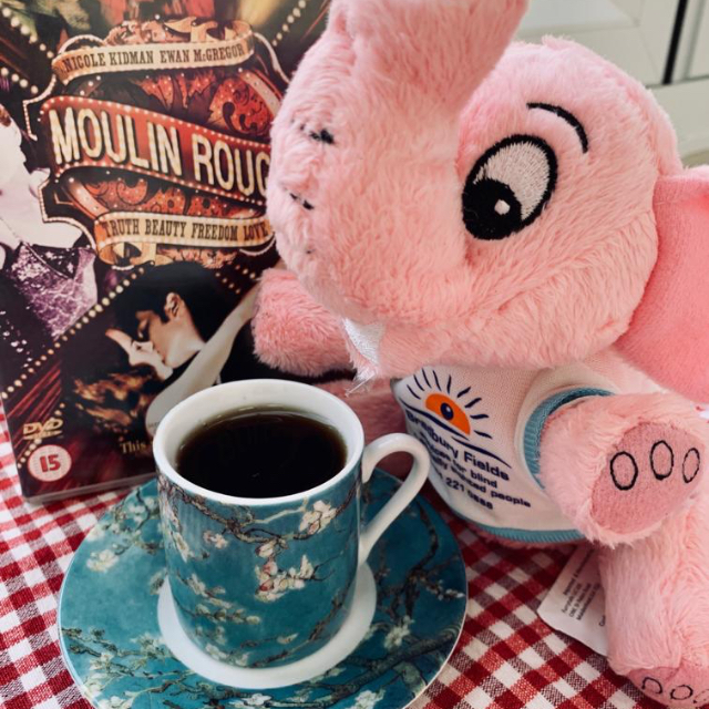 http://Close-up%20of%20Brad%20drinking%20coffee%20with%20a%20Moulin%20Rouge%20DVD.