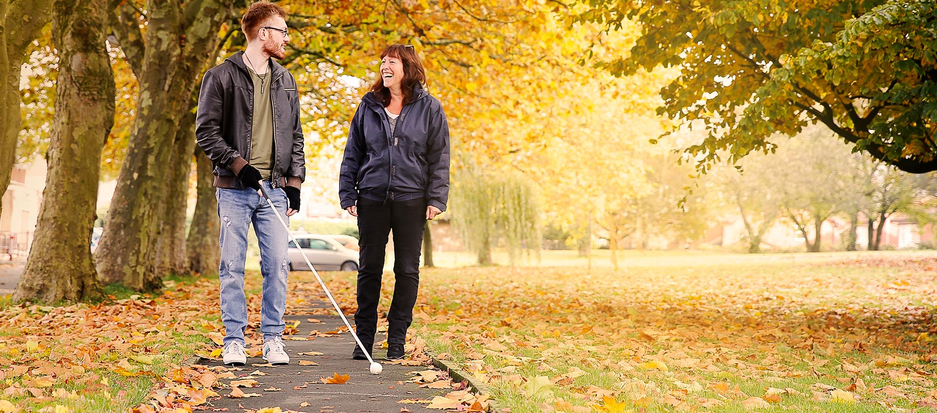 A visually impaired service user in an Autumnal outdoor setting having long cane training with a Rehabilitation Officer.