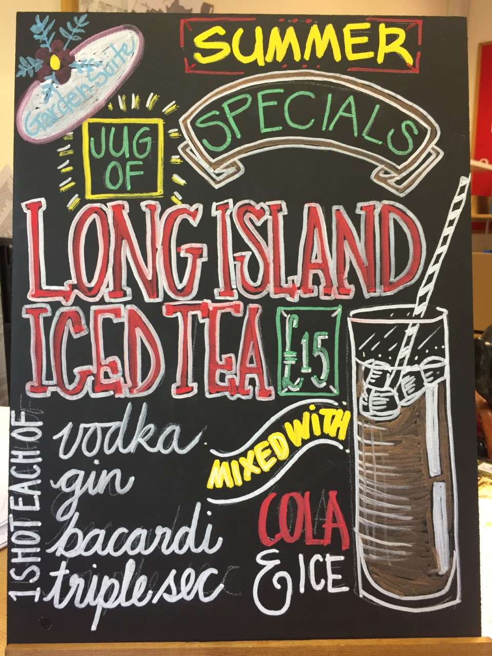 http://A%20colourful%20chalkboard%20with%20a%20drawing%20of%20a%20large%20jug%20with%20ice%20and%20a%20straw.%20It%20is%20advertising%20a%20pitcher%20of%20Long%20Island%20Iced%20Tea%20for%20£15.