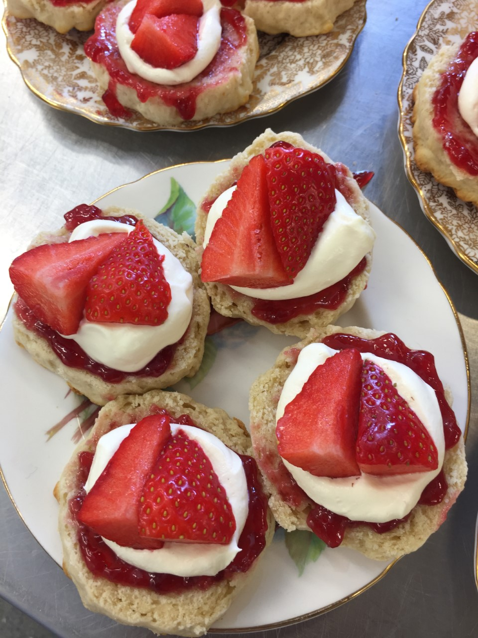 http://Four%20classic%20cream%20tea%20scones%20with%20jam,%20cream%20and%20fresh%20strawberries%20on%20top%20on%20a%20pretty%20vintage%20plate.