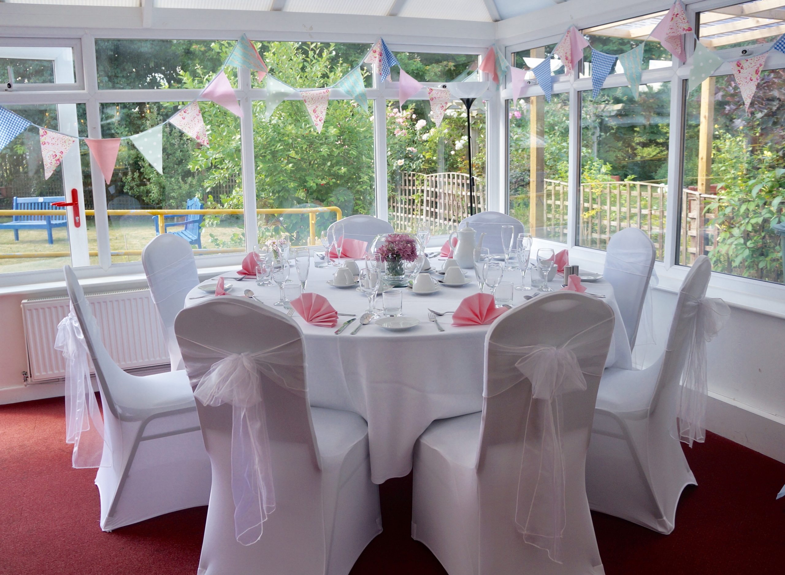 http://Eight%20place%20formal%20table%20setting%20with%20white%20linen%20and%20pink%20napkins.%20The%20chairs%20are%20dressed%20with%20white%20covers%20and%20large%20organza%20bows.%20The%20pastel%20coloured%20bunting%20frames%20the%20window%20showing%20the%20sensory%20garden%20on%20a%20sunny%20day.