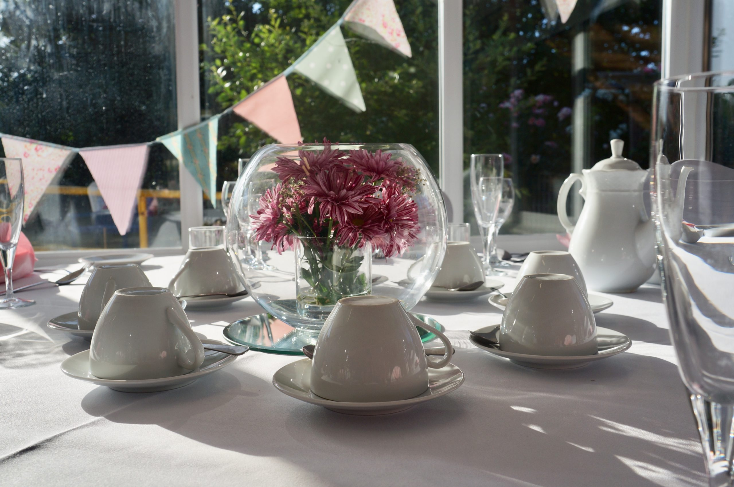 http://A%20close-up%20of%20an%20afternoon%20tea%20table%20setting.%20The%20sun%20is%20shining%20through%20the%20glass%20centrepiece%20filled%20with%20pink%20flowers%20and%20there%20is%20bunting%20and%20a%20view%20of%20the%20sensory%20garden%20in%20the%20background.