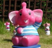 http://A%20colourful%20close-up%20of%20a%20Brad%20the%20Elephant%20plastic%20money%20box%20in%20a%20garden.%20He%20is%20pink%20with%20a%20pale%20blue%20and%20white%20striped%20t-shirt%20on%20and%20he%20is%20smiling%20and%20waving,%20there%20is%20green%20grass%20and%20two%20other%20money%20boxes%20in%20the%20background.
