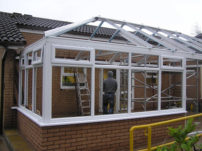 http://A%20colour%20photograph%20from%20outside%20the%20conservatory%20whilst%20still%20being%20built,%20the%20exterior%20walls%20and%20windows%20are%20complete%20but%20the%20interior%20walls%20are%20still%20to%20be%20taken%20down.