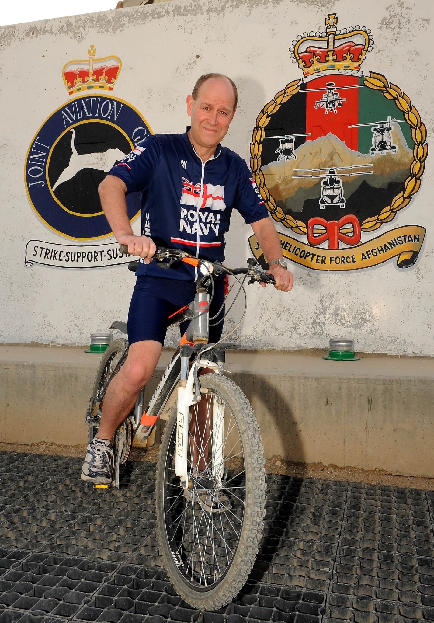 http://A%20volunteer%20wearing%20a%20Royal%20Navy%20top%20on%20a%20mountain%20bike%20in%20front%20of%20two%20forces%20logos%20painted%20on%20a%20wall.