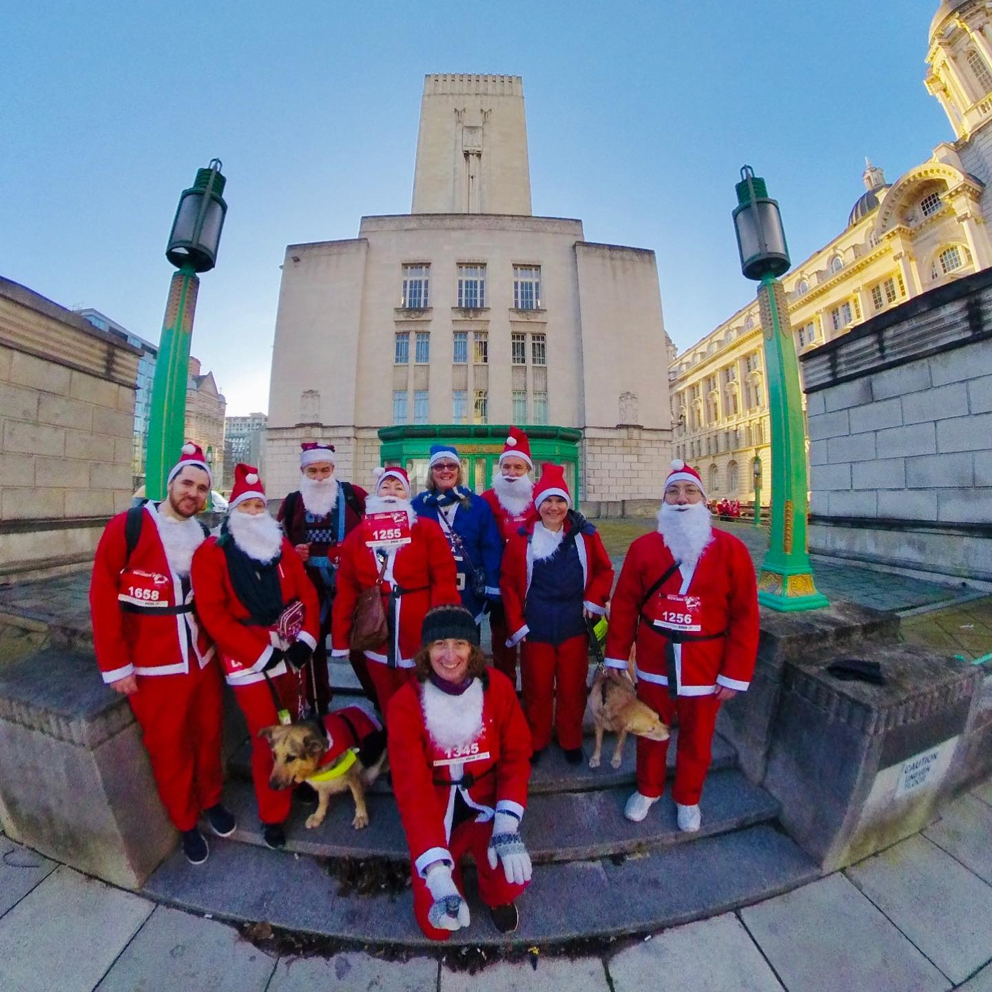 http://Nine%20service%20users%20and%20volunteers%20dressed%20as%20Santa%20with%20race%20numbers%20attached%20to%20their%20fronts%20standing%20outside%20the%20art-deco%20tunnel%20ventilation%20shaft%20at%20Liverpool%20waterfront.