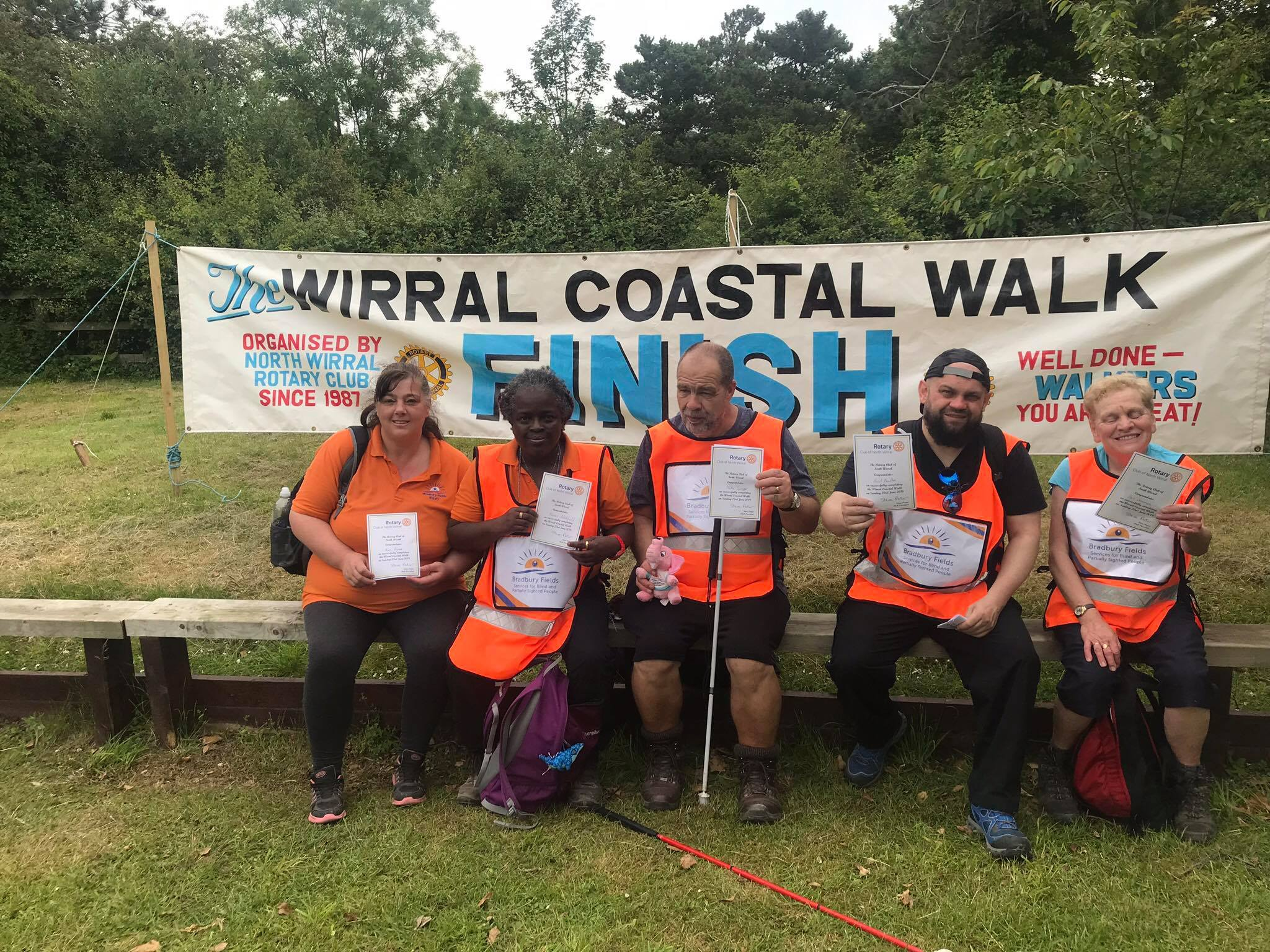 http://Five%20service%20users%20and%20volunteers%20sitting%20in%20front%20of%20a%20Wirral%20Coastal%20Walk%20banner%20showing%20off%20their%2010-mile%20certificates%20of%20completion.